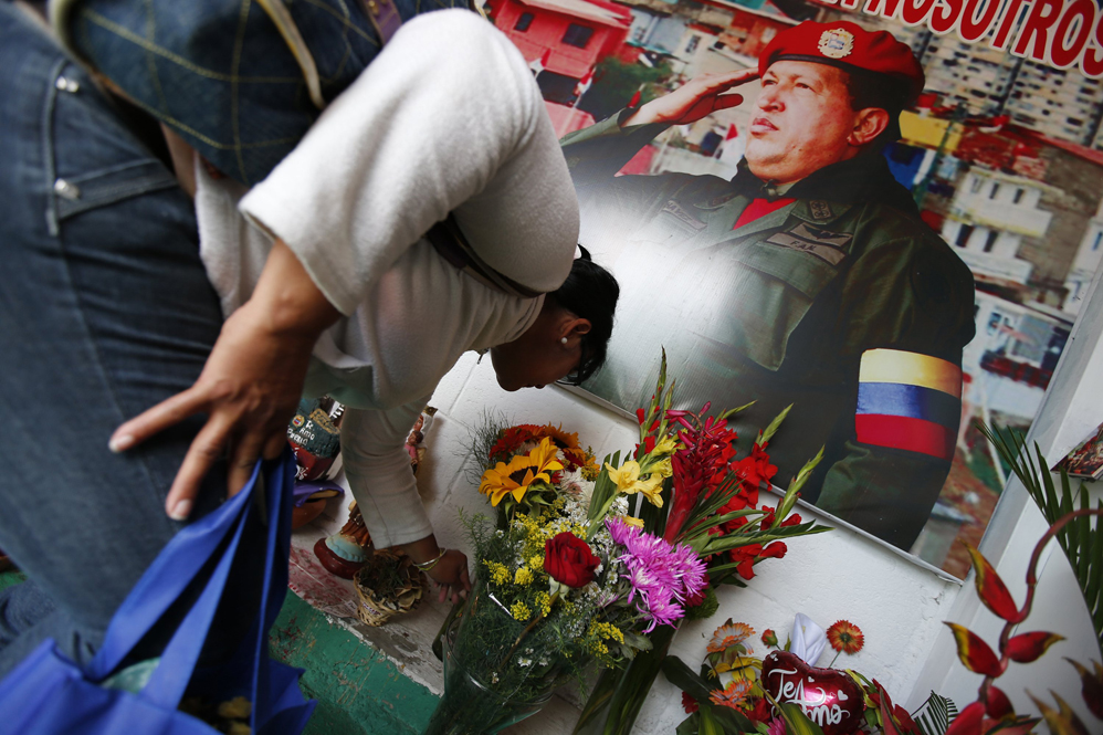 A woman places flowers inside a chapel dedicated to the late Venezuelan President Hugo Chavez, outside his mausoleum in Caracas