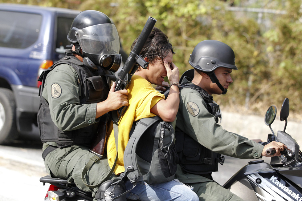 Anti-government protester is detained by national guard after small group of protester clash with guard at end of a march in Caracas