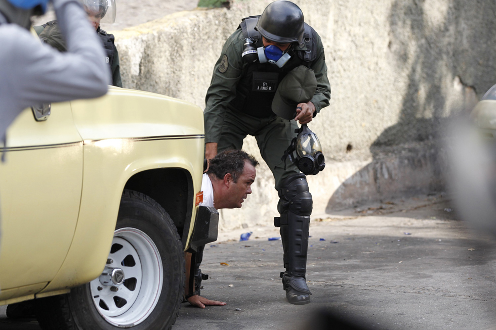 Anti-government protester is detained by national guard after clash with guard at end of a march in Caracas