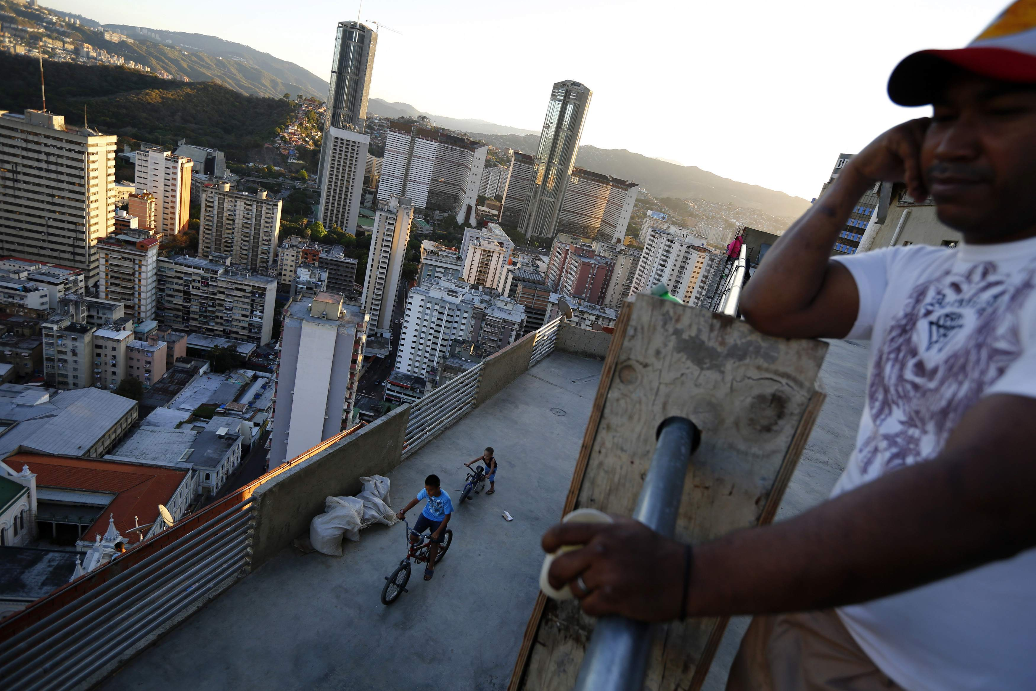 "Children ride bicycles on one of the top inhabited floors of the ""Tower of David"" skyscraper in Caracas"