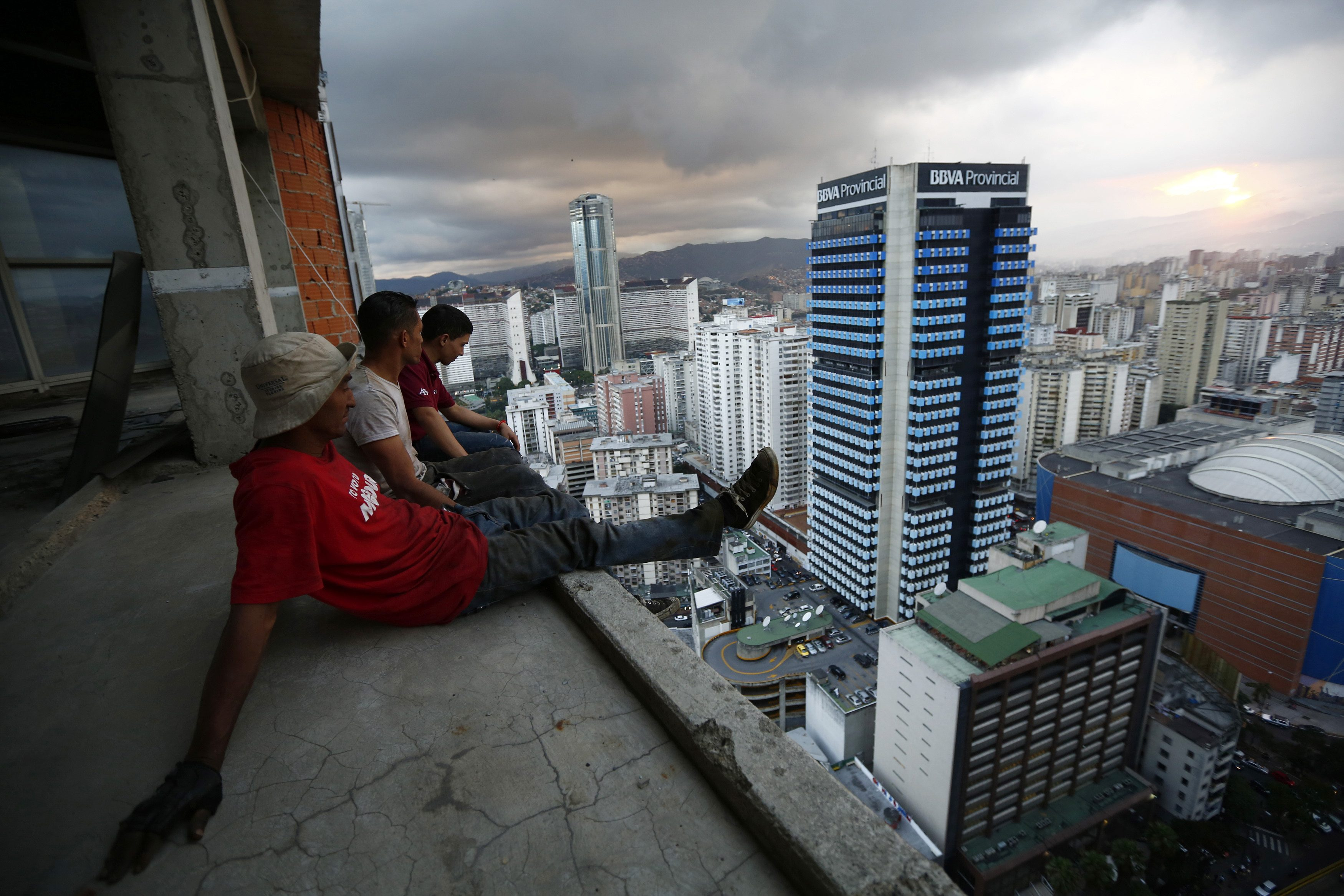 "Men rest after salvaging metal on the 30th floor of the ""Tower of David"" skyscraper in Caracas"