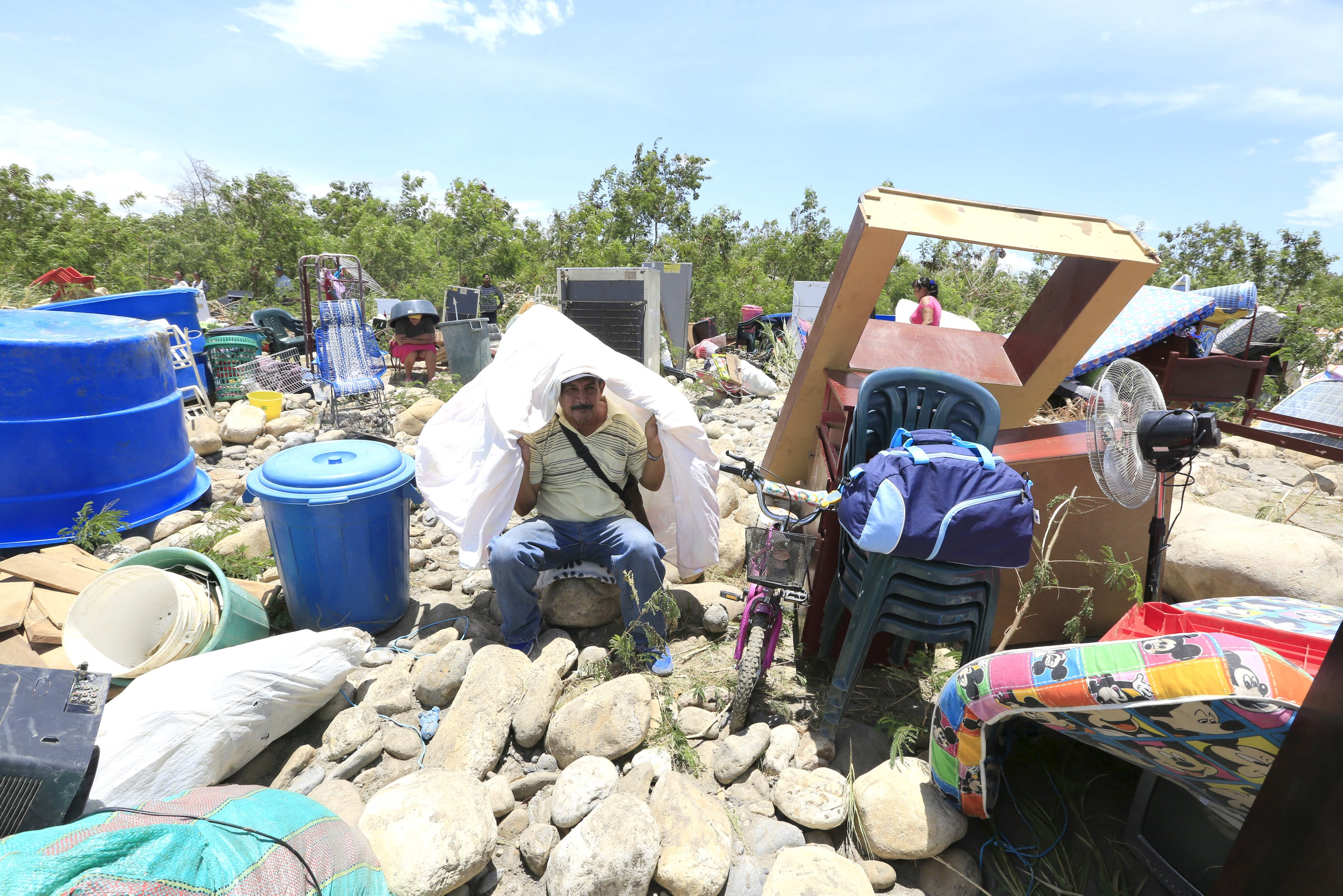 A man sits with his belongings after crossing the Tachira river border with Venezuela into Colombia, near Villa del Rosario village