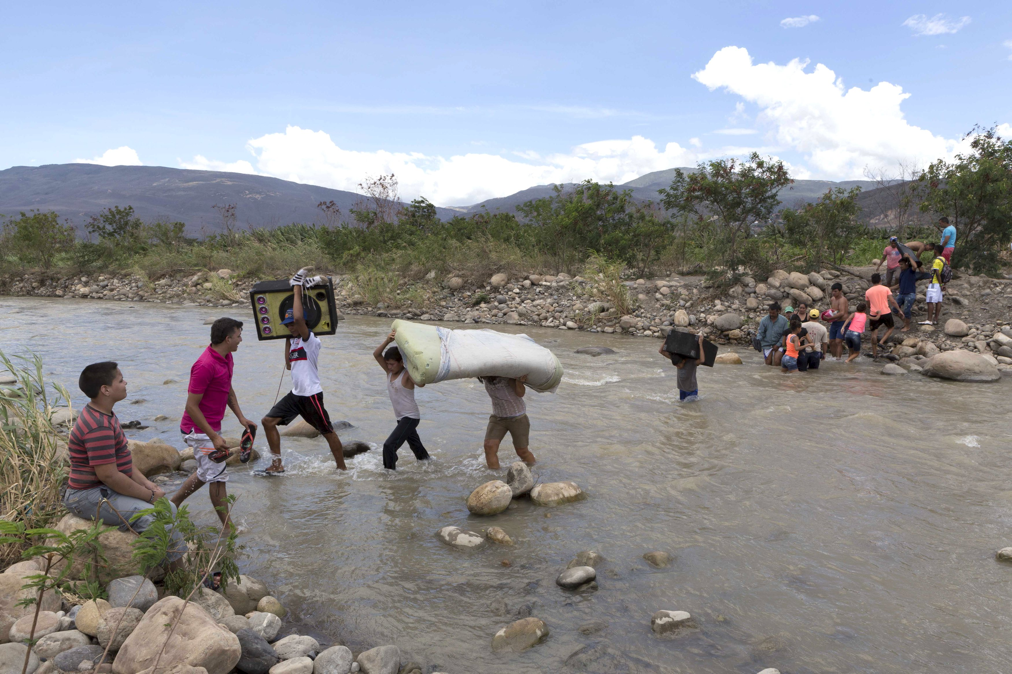 Colombian carry their belongings over from Venezuela as they cross the Tachira river close to Cucuta city, Colombia