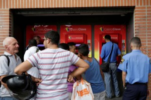 People line up to withdraw cash from an automated teller machine (ATM) outside a Banco de Venezuela branch in Caracas