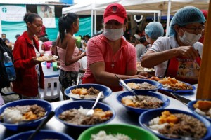 A woman serves food in a shelter for Venezuelan migrants in Cucuta