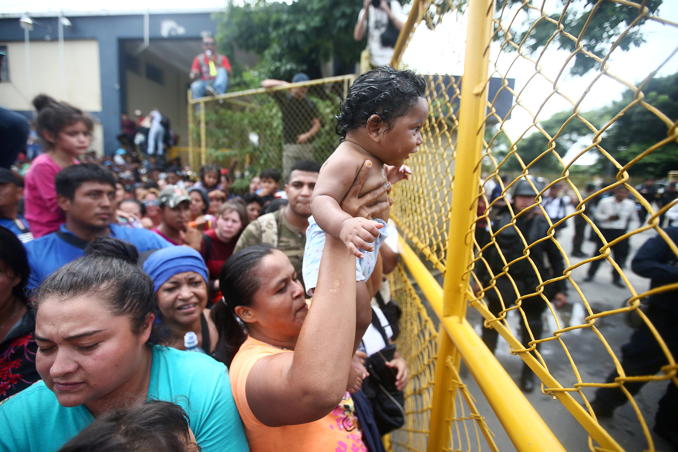 A Honduran migrant, part of a caravan trying to reach the U.S., holds a baby in front of a fence in the checkpoint between Guatemala and Mexico in Tecun Uman