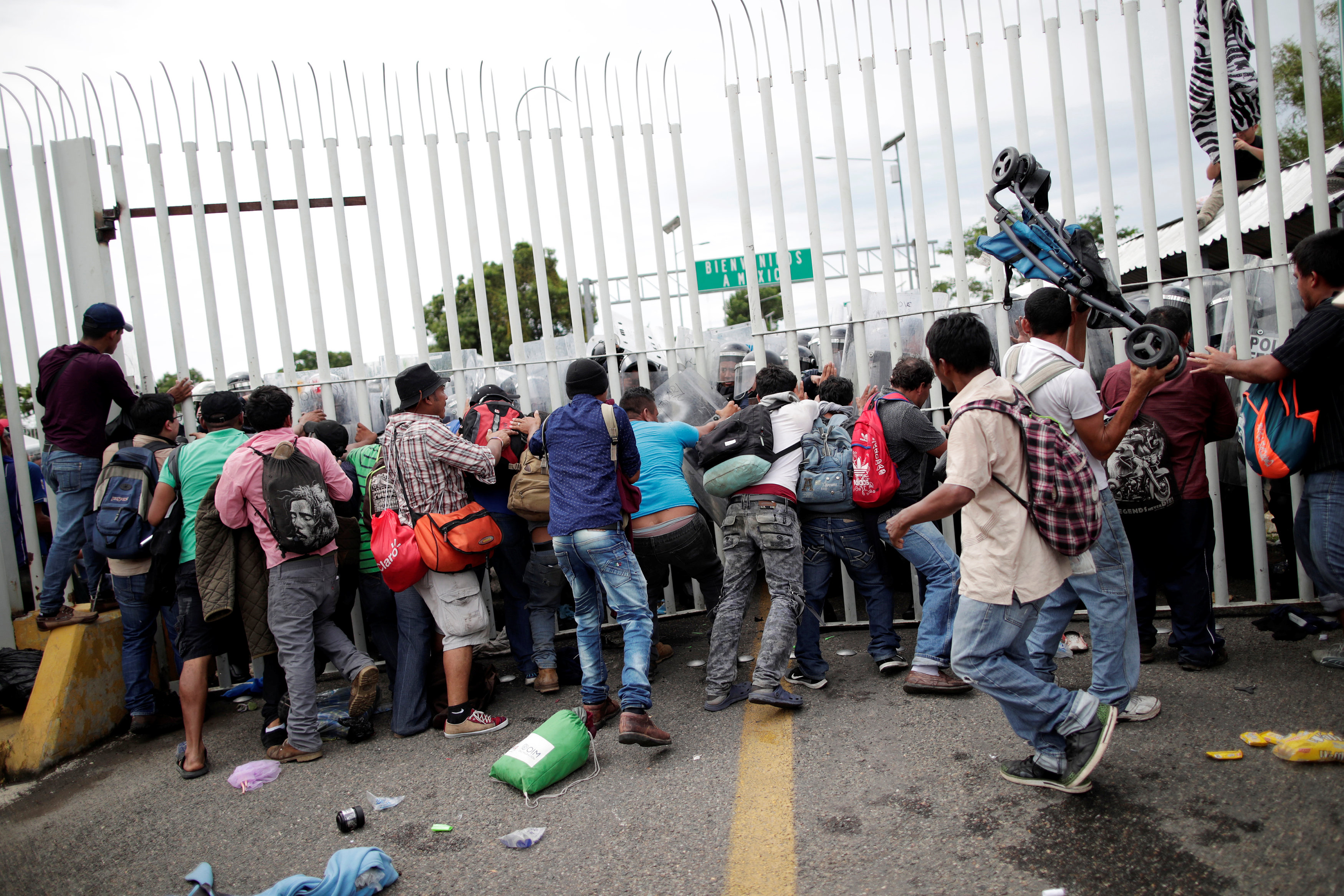Honduran migrants, part of a caravan trying to reach the U.S., push a fence to make their way into Mexico as federal riot policemen guard the border checkpoint, in Ciudad Hidalgo