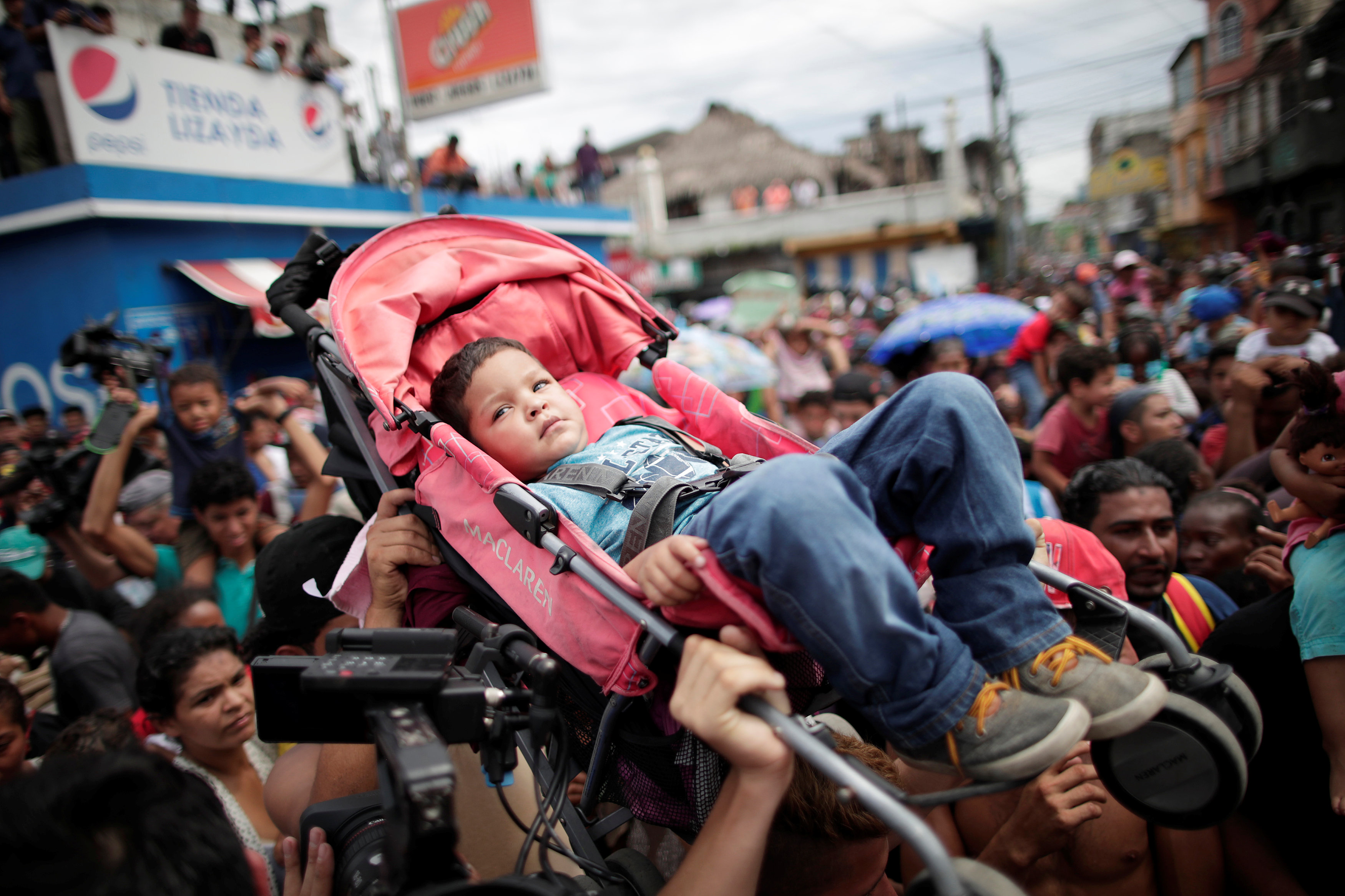 Honduran migrants, part of a caravan trying to reach the U.S., hold up a child in a stroll while, gathering at the Guatemalan border to cross into Mexico, in Tecun Uman