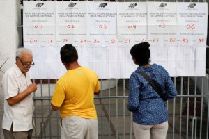People check electoral lists at a polling station during the municipal legislators election in Caracas
