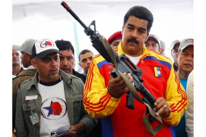 Venezuela's President Nicolas Maduro holds a weapon during a public destruction of confiscated weapons in Caracas