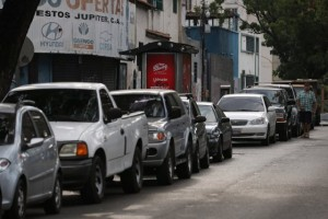 Motorists line up for fuel at a gas station during a blackout in Caracas