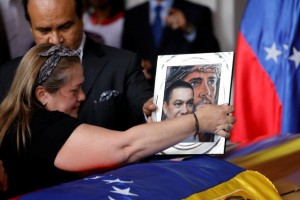 Luz Alban places an image of her brother Fernando Alban and Jesus Christ over his coffin during a ceremony at the National Assembly in Caracas