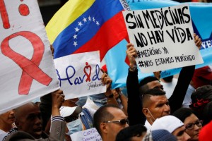 People carrying placards and shouting slogans take part in a protest due to the shortage of medicine outside the Health Ministry in Caracas